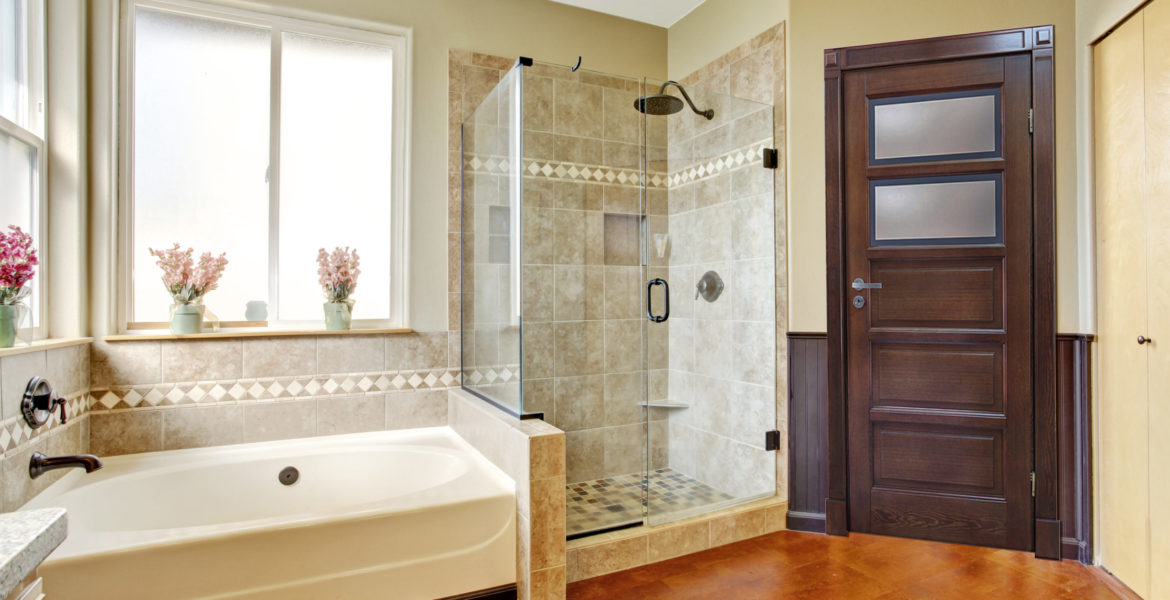 Bathroom interior with white bath tub, glass door shower and toilet